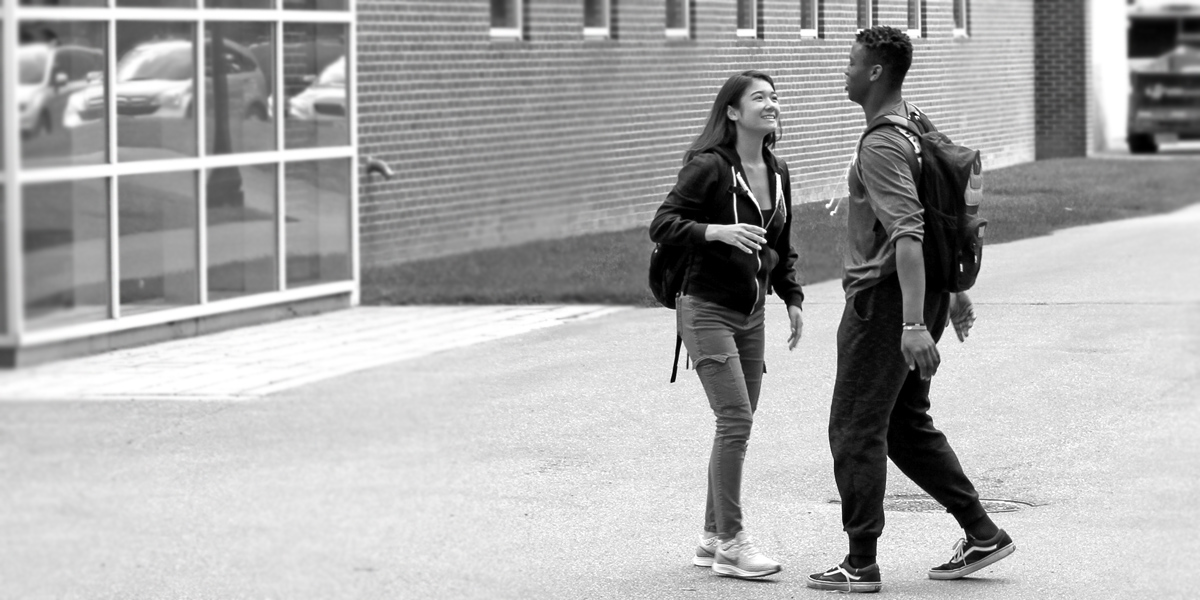 Two Bowdoin students greet each other outside of the Buck Fitness Center.