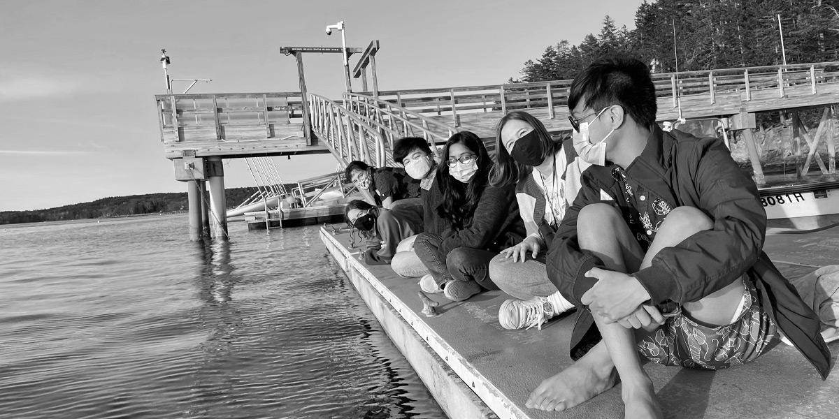 Students take a break on the dock at Bowdoin's Schiller Coastal Studies Center.