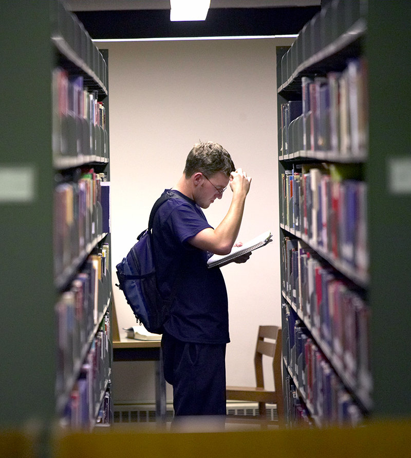 A student searches in the library stacks.