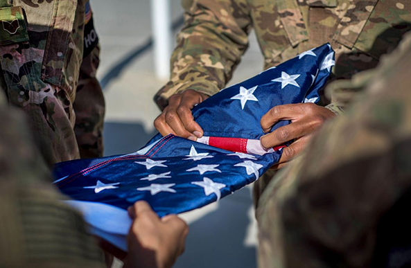 Soldiers fold a US flag