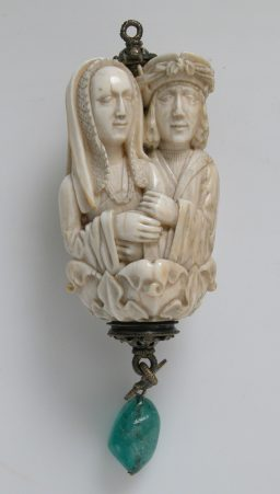 """Rosary Terminal Bead with Lovers and Death's Head,"" ca. 1500–1530, ivory, with emerald pendant, silver-gilt mount, BCMA Attribution to Chicart Bailly. The Metropolitan Museum of Art, New York, Gift of J. Pierpont Morgan, 1917"