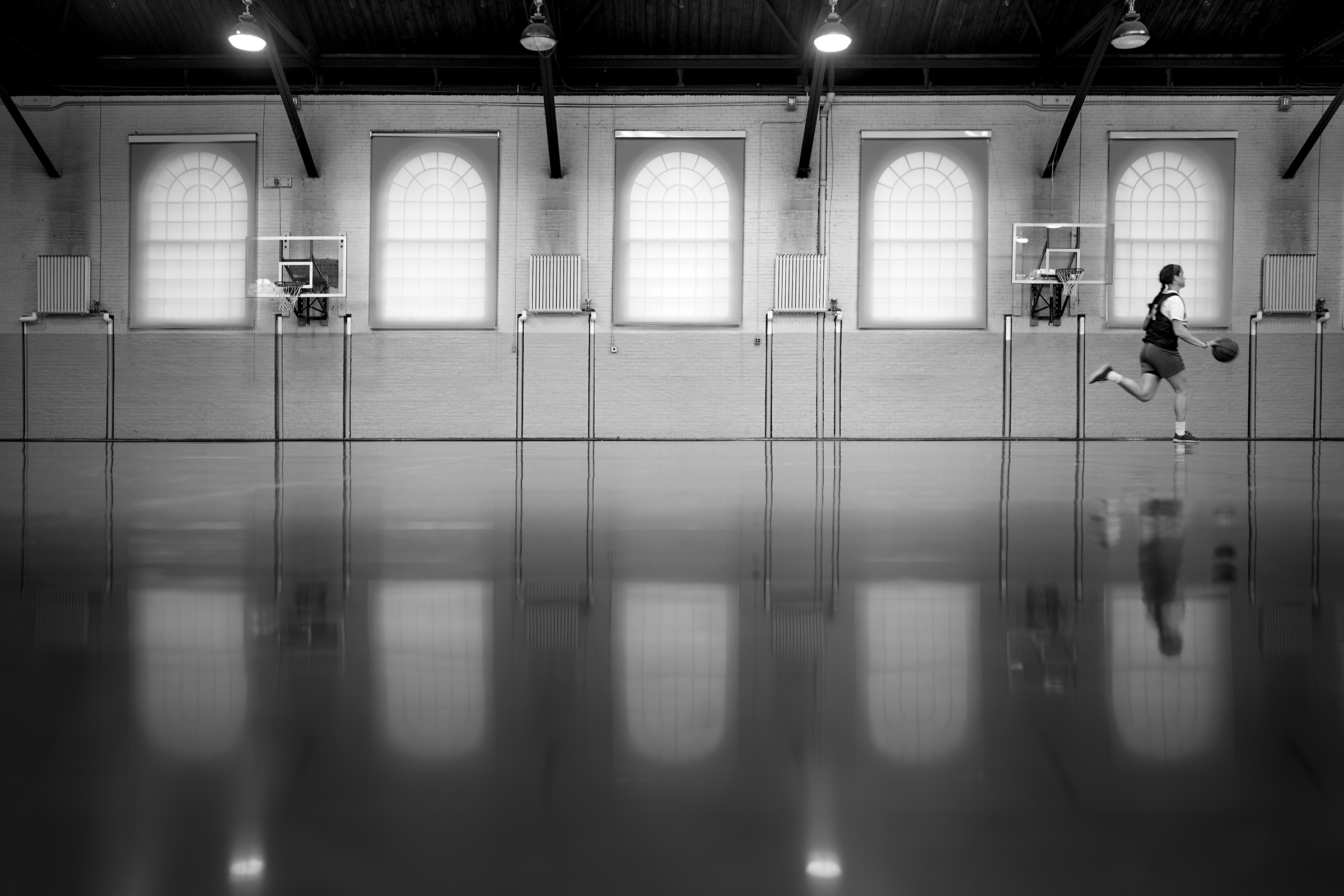 A student dribbles a basketball in Sargent Gym.