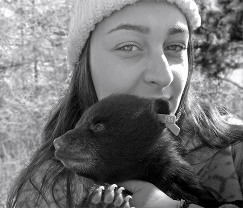 A student holds a bear cub in northern Maine
