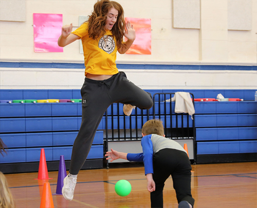Members of the basketball team play dodgeball with Carver students