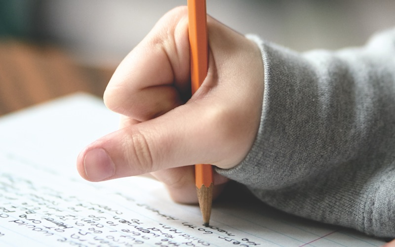 Student clenching a pencil, forcing the skin between their thumb and index finger back, so they can increase the pressure their pencil has on the paper.